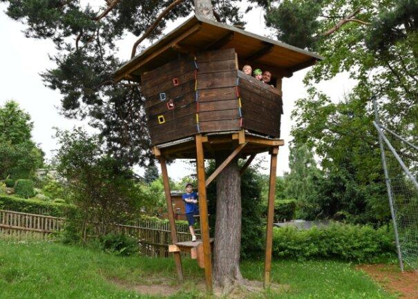 """Auf das Baumhaus im Garten der Auer Kindertagesstätte """"Spatzennest"""" hinauf dürfen immer nur drei Kinder - zwei, Emely Schreiber und Devin Leng (von links), sind schon oben mit Hausmeister Andreas Stief. An der Leiter unten wartet noch Nicholas Kropp."""