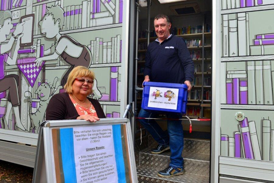 """Der Bücherbus der Kreis-und Fahrbibliothek ist weiterhin unterwegs. Leiterin Gabriele Hohmann weist auf die neuen Regeln hin: Der Bus darf von Nutzern nicht mehr betreten werden. Mitarbeiter wie Heiko Stiebinger geben """"Medientüten"""" oder Bücherboxen heraus."""