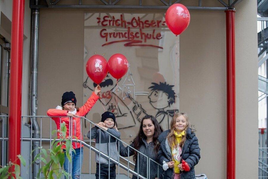 """An den Eingängen der Grundschule grüßen """"Vater und Sohn"""". Familie Müller freut das: Ellie, Oskar, Mutti Sabrina und Mia (von links)."""