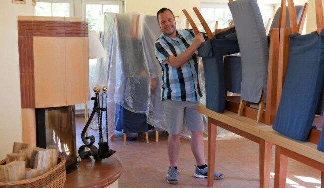Betriebsleiter und Küchenchef Frank Kirschberger bereitet das Kaminzimmer für die Eröffnung vor.