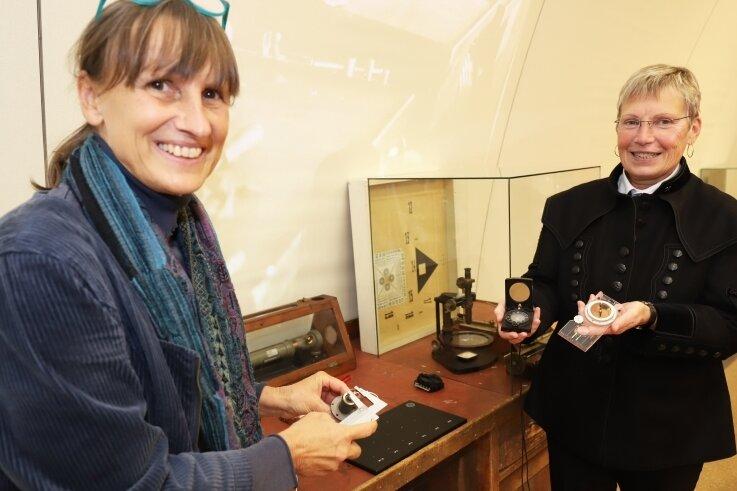 Ausstellungsgestalterin Kirsten Helmstedt (l.) und Museumsdirektorin Andrea Riedel an einem historischen Arbeitstisch, der in der neuen Sonderausstellung zur Geschichte der Freiberger Präzisionsmechanik steht.