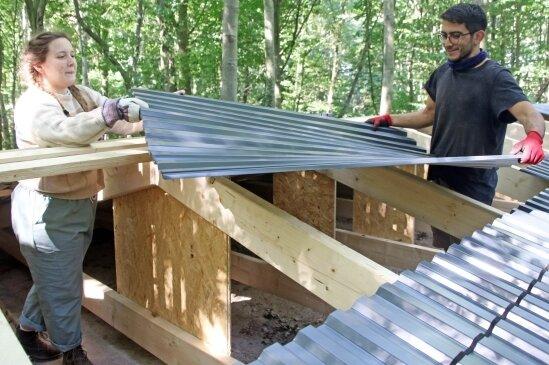Elsa Heebner aus Kanada und Mert Sumer aus der Türkei decken das Notdach über der Gruft.