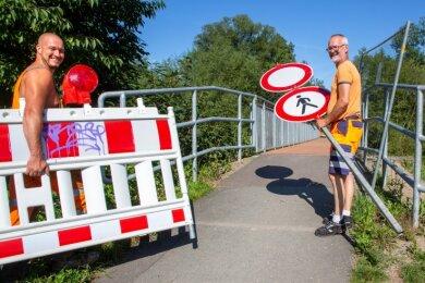 Die Schwarze Brücke über die Flöha ist wieder befahrbar. Die Bauhofmitarbeiter Roland Melzer (links) und Mathias Auerbach räumten am Donnerstag die Absperrungen zur Seite.