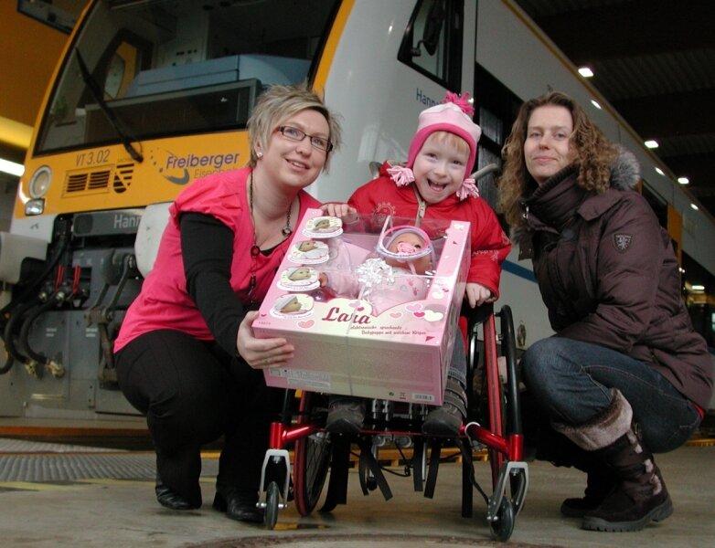 """<p class=""""artikelinhalt"""">Die auf den Rollstuhl angewiesene Hannah bekam heute neben der Geldspende von Sandy Eyring (l.) von der Freiberger Eisenbahn noch eine Puppe als Geschenk, worüber sich auch ihre Mutti freute. </p>"""