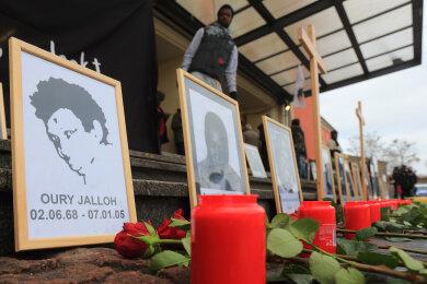 An einem Bild des Asylbewerbers Oury Jalloh (l) sind vor Beginn einer Demonstration zu seinem zehnten Todestag 2015 Blumen und Kerzen aufgestellt.