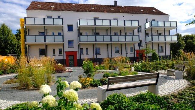 """Mit viel Grün und einem Rondell mit Bänken ist der Außenbereich am """"Haus Gesundheit"""" zu einer Wohlfühloase geworden."""