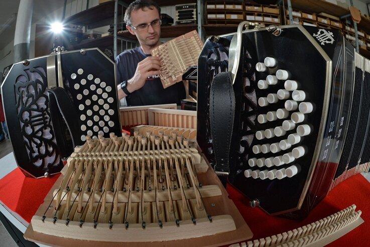 Mit Fingerspitzengefühl montiert Handzuginstrumentenmacher Ralf Skala in Klingenthal ein Bandoneon. Die Manufaktur im Vogtland hält die Fertigung in Tradition der legendären AA-Instrumente hoch.