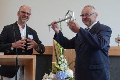 Architekt Ralf Wilhelmi (links) hat an den Gemeindevorsteher Uwe Herrmann den symbolischen Schlüssel übergeben.