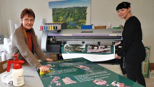 In der Werkstatt der Eibenstocker Grafikdesignerin Ina Gläser (l.) sind die Informationstafeln für den Bergbaulehrpfad in Eibenstock entstanden. Beim Aufziehen hilft ihr Mitarbeiterin Kerstin Kluge.