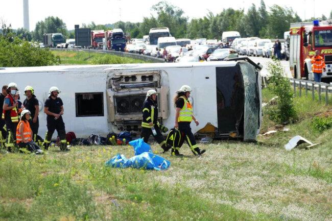 Rettungskräfte sind an der Unfallstelle im Einsatz. Auf der Autobahn 13 bei Schönwald (Dahme-Spreewald) südöstlich von Berlin ist ein Reisebus verunglückt. Dabei wurden mehrere Menschen verletzt.