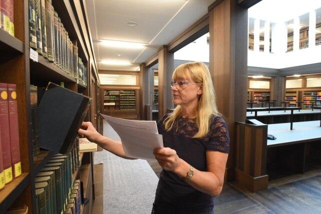 Im großen Lesesaal der Bibliothek im zweiten Stock stehen überwiegend schwere Bände wie Chroniken, Lexika und Enzyklopädien in den Regalen. Umzugsleiterin Dagmar Hesse kontrolliert einige Exemplare.