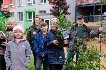 Marko Hofmann von Fielmann; Bianca Beyer, stellvertretende Einrichtungsleiterin des Naturhortes, Jörg Schöne von der Gärtnerei Schöne (hinten v. l.) freuen sich mit Zoe, Chiara, Jonas und Maria (vorn v. l.) über das neue Grün.