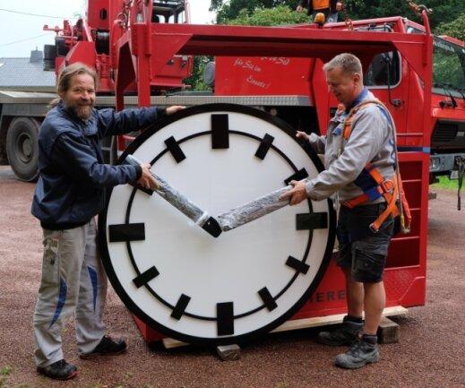 Die Turmuhrenbauer Rigo Rudel (links) und Silvio Lisker haben am Mittwoch Ziffernblätter und Zeiger der vier neuen Kirchturmuhren in Niederwürschnitz eingebaut.