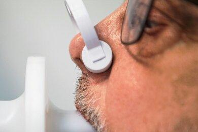 Symptom Luftnot: Ein Long-Covid-Patient lässt seine Lungenfunktion mit einem Bodyplethysmographen überprüfen.