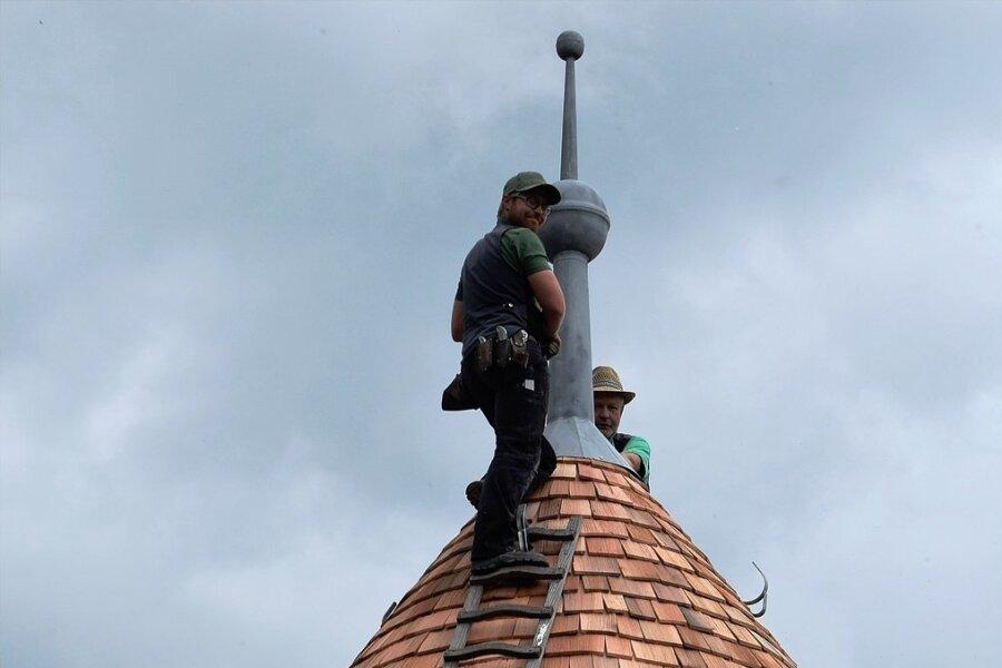 Tobias und Ulf Voit vom gleichnamigen Dachdecker-Fachbetrieb in Netzschkau befestigen die Spitze mit der Kapsel auf dem untersten Turm der Elsterberger Burgruine.