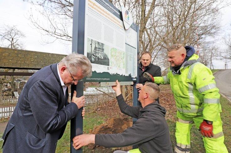 Matthias Lißke (l.), Bürgermeister Martin Antonow (Mitte hinten), Ronny Venus (r.) und Daniel Büttner haben am Dienstag die Welterbe-Informationstafel in Brand-Erbisdorf aufgestellt.