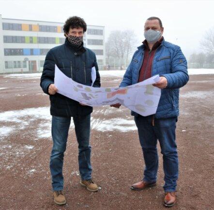 Niederwiesas Bürgermeister Raik Schubert (links) und Bauamtsleiter Lars Schuster vor der Fläche für die neue Sporthalle.
