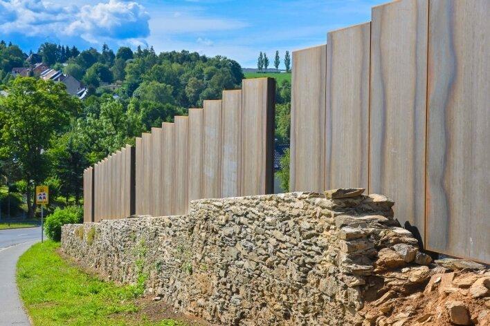 Die Schallschutzwand aus Cortenstahl in Friesen an der B 94 hinter der wieder aufgemauerten historischen Schlossmauer.