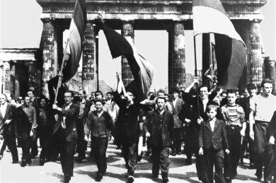 Ost-Berliner marschieren am 17. Juni 1953 mit wehenden Fahnen vom Ost-Sektor aus durch das Brandenburger Tor.