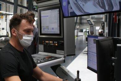 So sieht der Arbeitsplatz eines Zerspanungsmechanikers bei Porsche aus: Erik Schmiedel steuert per Computer eine hochmoderne Fräsmaschine, die eine Tür bearbeitet.