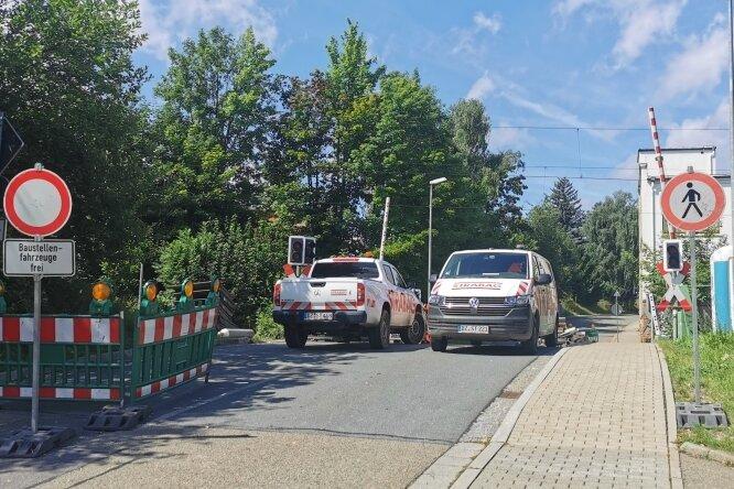 Fahrzeuge des Bau-Riesen Strabag blockieren den Bahnübergang Schlossstraße in Netzschkau: Dort, aber auch an mehreren anderen Abschnitten im Vogtland, finden Gleiserneuerungsarbeiten statt.