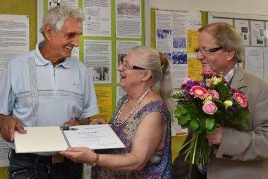 """Aus den Händen von Heidi und Thomas Petzoldt nahm Falk Naumann (links) die """"Goldene Ehrennadel des Kulturbundes"""" entgegen."""
