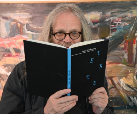 """Der Schriftsteller Hans Brinkmann mit seinem Buch """"Texte über Künstler"""" in der Galerie Laterne."""