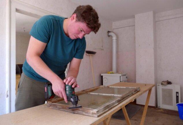 Derzeit kümmert sich Felix Kortung um die Fenster, von denen er zunächst die alte Farbe abschleift.