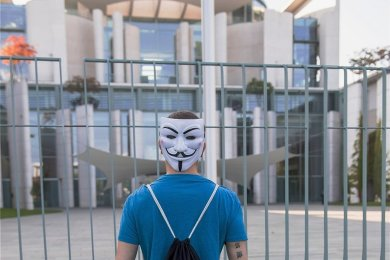 """Das Hier und Jetzt als gigantische Lüge geheimer Mächte interpretiert: Demonstrant einer antidemokratischen """"Querfront-Mahnwache"""" vor dem Kanzleramt in Berlin."""
