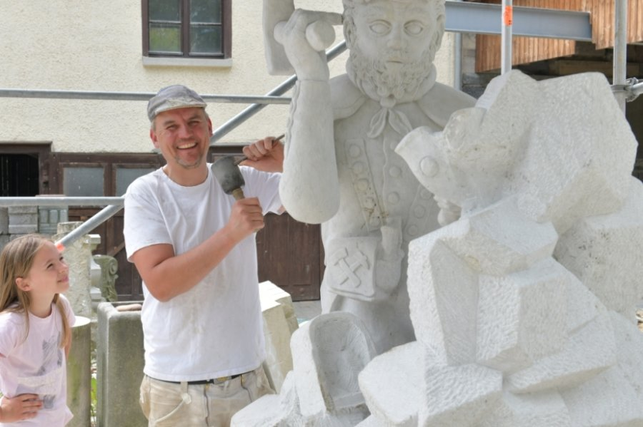 Sebastian Haupt, Steinmetz und Steinbildhauermeister aus Oberbobritzsch, bei seinen Arbeiten an der Bergmannsfigur. Tochter Alienna (9) schaute öfter dabei zu.