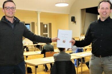 Björn Rosenkranz (links) übergibt an Bürgermeister Dirk Fröhlich den Brandschutzbedarfsplan.