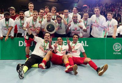 Die Spieler vom SSV Jahn 1889 Regensburg jubeln mit der Meisterschale nach ihrem Finalsieg gegen den VFL 05 Hohenstein-Ernstthal bei der Deutschen Futsal-Meisterschaft in Zwickau.