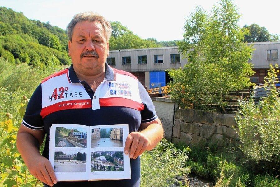 Michael Held mit einem Buch, dass das Hochwasser 2013 auf dem Firmengelände zeigt. Hinter ihm kann man gut erkennen, bis zur welcher Stelle die Hochwasserschutzmaßen erledigt sind: Links von einer schwarzen Linie ist die Schutzmauer fertig. Rechts davon ist die Wand aus großen Steinen deutlich niedriger.