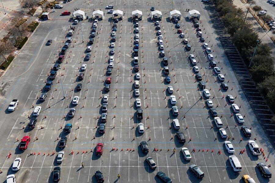 Massenimpfung in Houston im US-Bundesstaat Texas per Drive-in-Verfahren: Hunderte Autos stehen auf einem Parkplatz in einer Schlange, während die Fahrer darauf warten, gegen das Coronavirus geimpft zu werden.