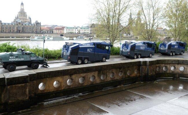 Wasserwerfer und ein Räumfahrzeug der Polizei stehen am Ufer der Elbe. Ein Großaufgebot der Polizei setzte das Versammlungsverbot gegenüber geplanten Kundgebung von Kritikern der Corona-Maßnahmen der Bundesregierung durch. Die Versammlungsbehörde hatte eine geplante Demonstrationen der Initiative «Querdenken351» und Ersatzveranstaltungen untersagt.