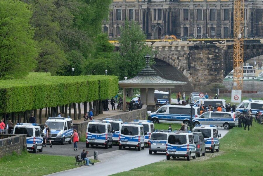 Polizisten stehen mit Einsatzfahrzeugen am Ufer der Elbe.