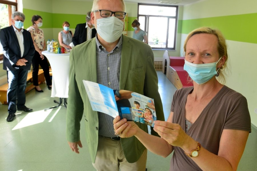 Maria Heyn, Leiterin der Familienberatungsstelle im Diakonischen Werk, zeigt Sozialstaatssekretär Uwe Gaul die neue Broschüre.