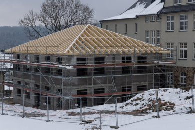 Als die Dachkonstruktion auf dem Anbau war, zog noch einmal der Winter ein. Sobald wie möglich sollen die Arbeiten weitergehen.