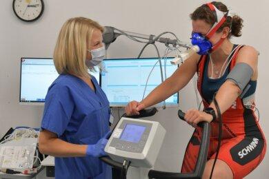 Kristin Krumbiegel macht sich bereit für den Belastungstest: Wie fit ist die 33-Jährige fünf Monate nach ihrer Coronainfektion? Carolin Lippert, medizinisch-technische Assistentin, prüft, ob alles sitzt.