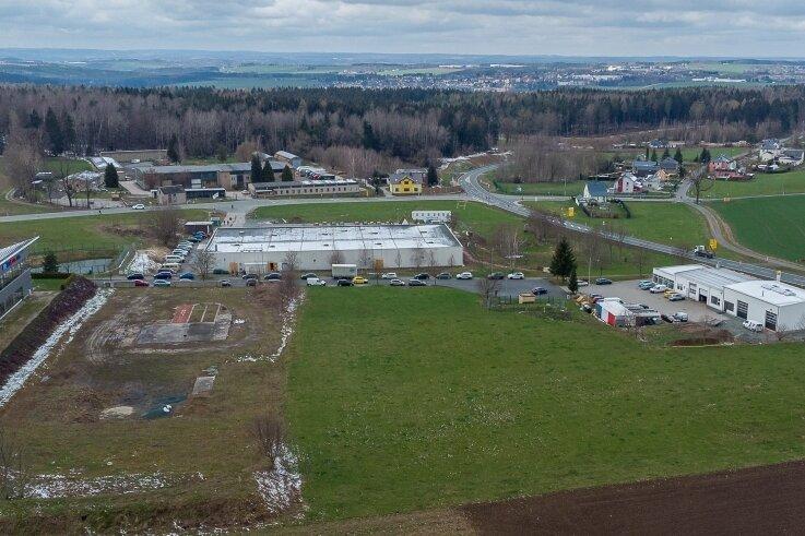 Das Kompetenzzentrum Brand- und Katastrophenschutz soll auf dieser Freifläche im Gewerbegebiet Eich entstehen: Im Hintergrund das aktuelle Impfzentrum des Vogtlandkreises, rechts im Bild ein Renault-Autohaus.
