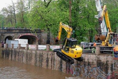 Arbeiter versuchten am Donnerstag zunächst, die Maschine zu stabilisieren. Als das misslang, wurde der Bagger mit einem Kran aus dem Fluss gehoben.