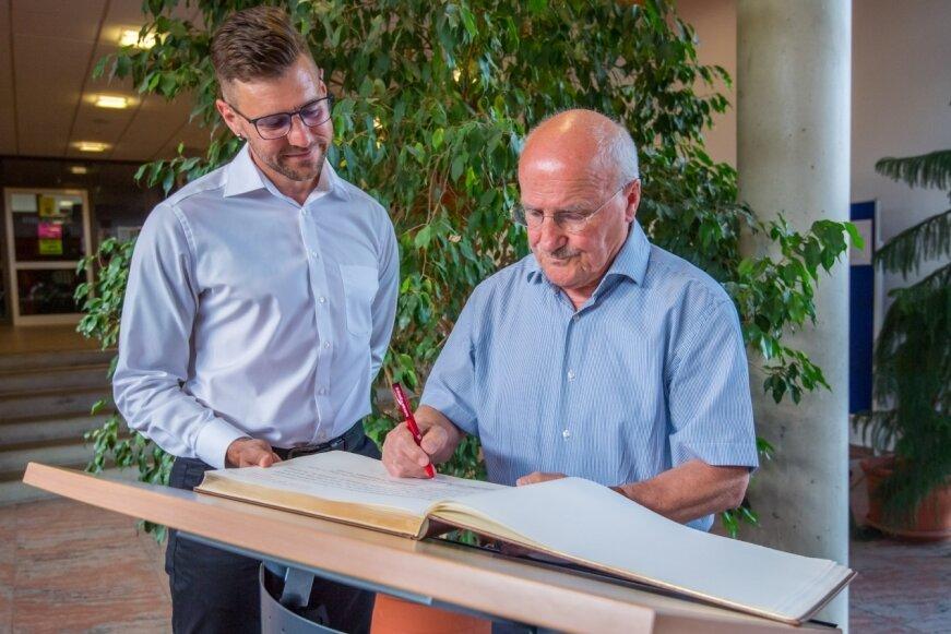 Dietmar Sommerfeld trägt sich im Beisein von Bürgermeister Sascha Thamm (links) in der Oberschule des Ortes ins Goldene Buch der Gemeinde Neukirchen ein. Damit wird er für sein langjähriges ehrenamtliches Engagement geehrt.