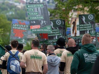 Teilnehmer eines rechten Aufmarsches der Partei «Der dritte Weg» gehen eine Straße entlang.