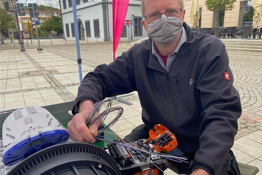 Telekom-Monteur Uwe Schädlich zeigt auf dem Zwickauer Hauptmarkt, wie Glasfaserkabel durch ein Schweißgerät miteinander verbunden werden können.