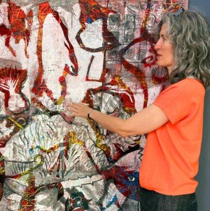 """Galerie-Betreuerin Simone Mende an dem Bild """"Das ist alles nur in meinem Kopf"""" von der Sebnitzerin Danjana Brandes. Die Ausstellung in der """"Galerie Inselsteig"""" ist noch bis zum 12. September zu sehen."""