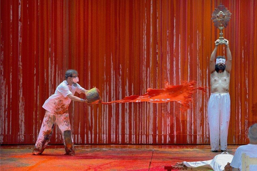 """Ein Malassistent schüttet rote Farbe auf einen Statisten der Festspiele: Das Bühnenbild der """"Walküre"""" wurde in diesem Jahr von """"Blutkünstler"""" Hermann Nitsch gestaltet."""