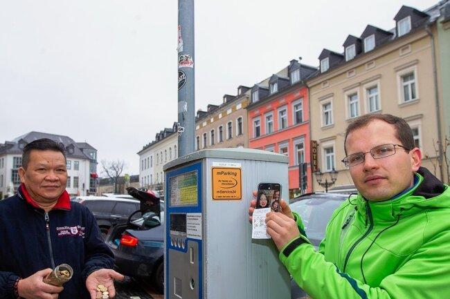 Auch wenn ein Aufkleber am Automaten noch für das digitale Parkticket wirbt: Seit April sind Maximilian Hahn und sein Schwiegervater Men Le Van auf dem Plauener Klostermarkt wieder auf Münzgeld angewiesen.