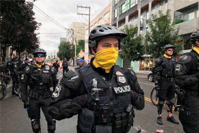 """US-Polizisten in Seattle Anfang Juli bei einem Protest gegen Rassismus und Polizeigewalt. Die Veröffentlichung gehackter Polizeidaten aus den USA (""""BlueLeaks"""") zieht jetzt Kreise bis ins Vogtland."""