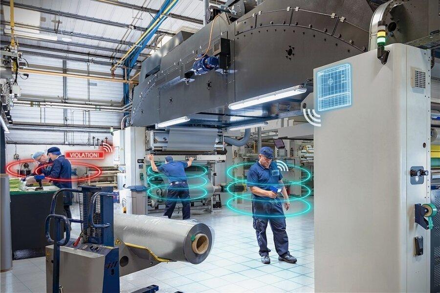Das bearbeitete Foto zeigt die Funktionsweise des Siemens-Systems zur Sicherung der Abstandsregeln. Kommen sich die Mitarbeiter zu nahe, ertönt ein Warnsignal, das hier rot dargestellt wird.