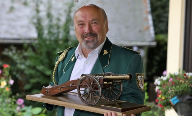 Hermann Scherzer zeigt den Wanderpokal in der Form einer Schützen-kanone.